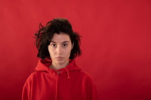 Menina morena exausta com um capuz vermelho posando olhando para a frente