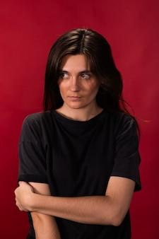 Menina morena exausta, de cabelos compridos e camiseta preta, parece estressada e nervosa