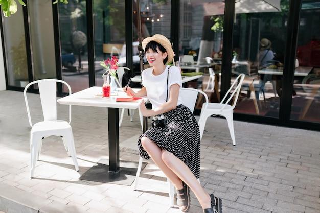 Menina morena feliz de saia preta e camisa branca, sentada em um café ao ar livre e aprecia a vista da cidade de bom humor