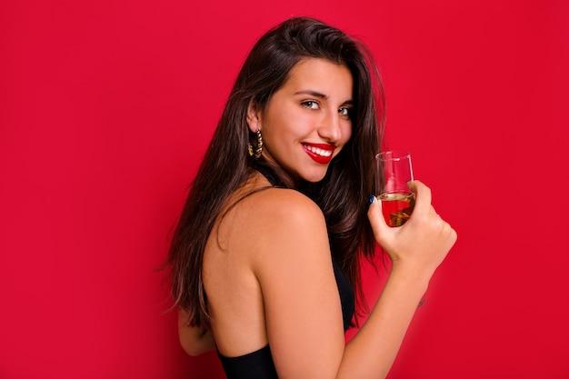 Menina morena feliz sorrindo para a câmera com uma taça de champanhe.