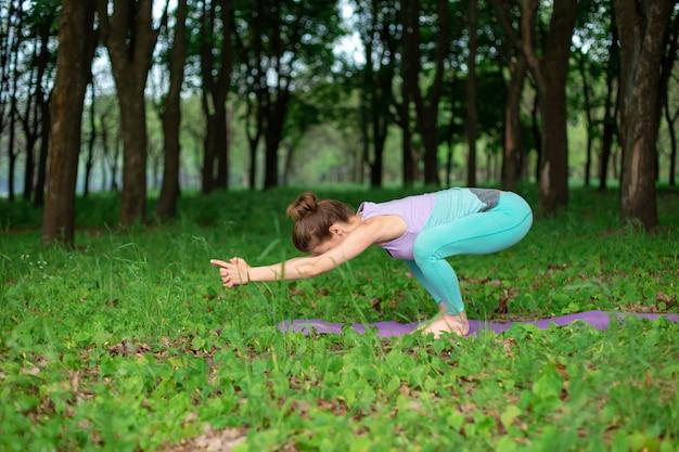 Menina morena fina pratica esportes e executa poses de ioga bonitas e sofisticadas em um parque de verão