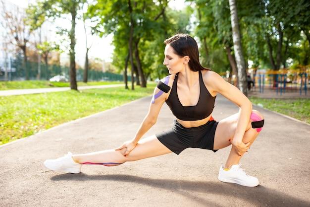 Menina morena flexível com corpo perfeito se aquecendo ao ar livre, praticando estocadas laterais profundas