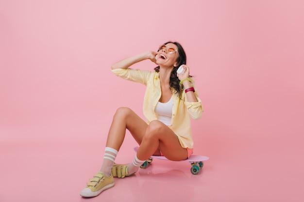 Menina morena glamorosa com pele bronzeada, sentada no longboard com as pernas cruzadas. retrato interior de mulher hispânica romântica de tênis amarelo, ouvindo música em fones de ouvido.