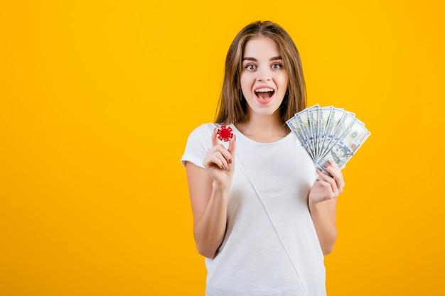 Menina morena grita animado com ficha de poker vermelho e notas de cem dólares na mão isolado sobre o amarelo