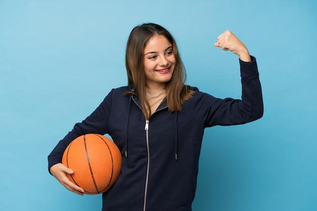 Menina morena jovem isolado azul com bola de basquete