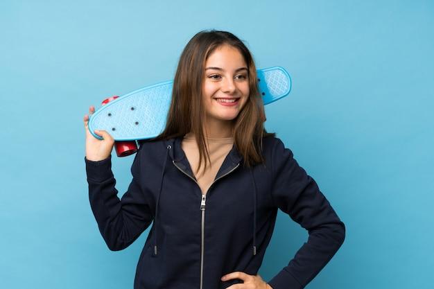 Menina morena jovem isolado azul com skate e olhando de lado
