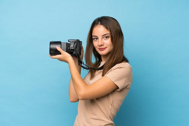 Menina morena jovem isolado azul com uma câmera profissional