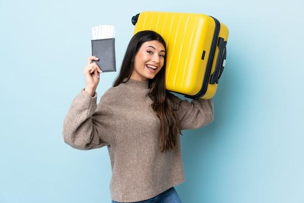 Menina morena jovem isolado parede azul em férias com mala e passaporte