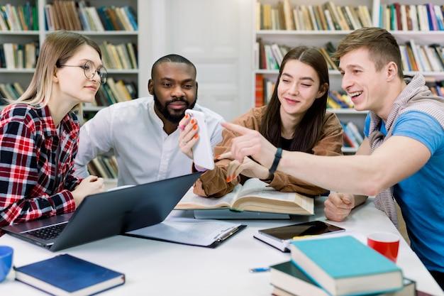 Menina morena jovem muito satisfeita, mostrando para seu grupo de estudantes de raça mista feliz vídeo ou aplicativo útil no smartphone