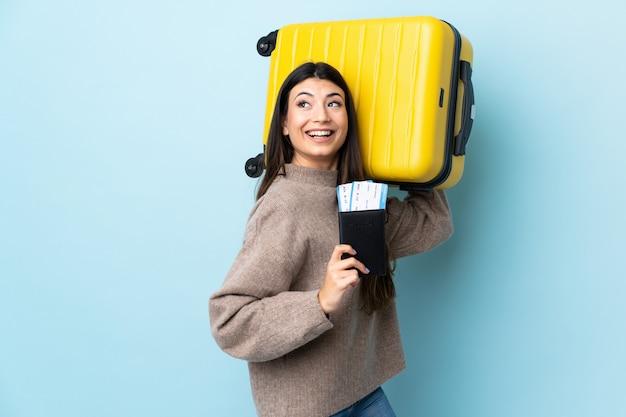 Menina morena jovem muro azul em férias com mala e passaporte