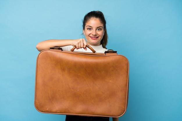 Menina morena jovem sobre azul isolado, segurando uma mala vintage