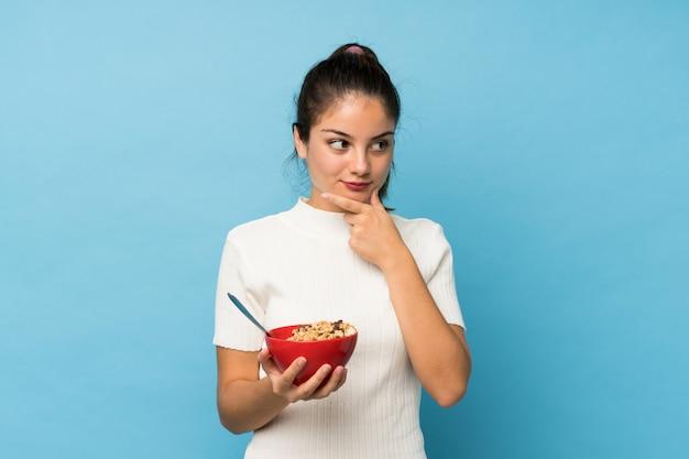 Menina morena jovem sobre azul isolado, segurando uma tigela de cereais e pensando