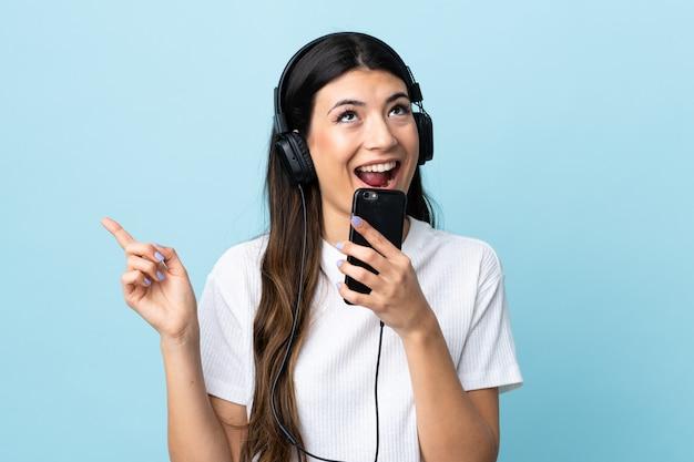 Menina morena jovem sobre música de parede azul isolado com um celular e cantando