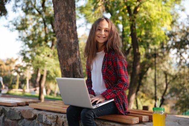 Menina morena jovem sorridente, sentado no banco com o computador portátil