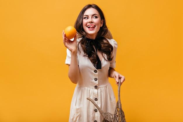 Menina morena legal em um vestido de algodão com laço em volta do pescoço está segurando uma laranja e lambendo.