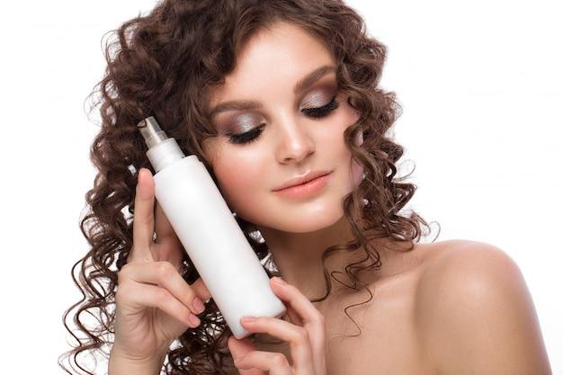 Menina morena linda com um cabelo perfeitamente encaracolado com borrifador e maquiagem clássica. rosto bonito.