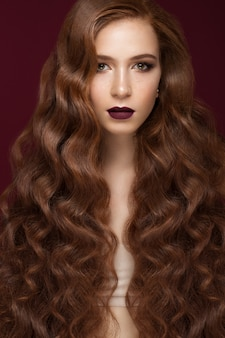 Menina morena linda com um cabelo perfeitamente ondulado e maquiagem clássica. rosto bonito.