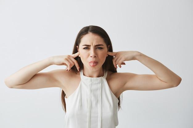 Menina morena linda descontente, fechando os ouvidos com os dedos do ruído, mostrando a língua.