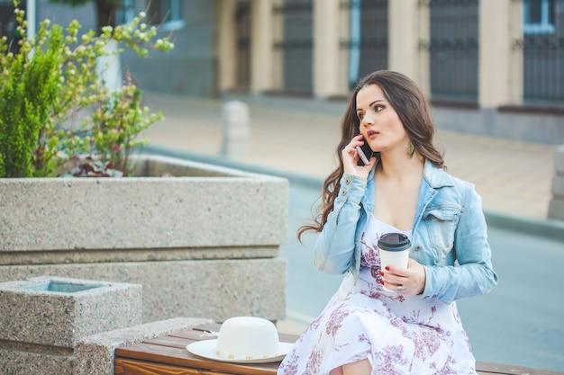 Menina morena linda em uma jaqueta jeans falando ao telefone, sentado em um banco na cidade e segurando um café