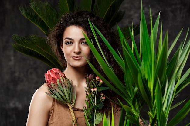 Menina morena linda jovem em plantas tropicais ao longo da parede cinza