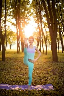 Menina morena magra pratica esportes e realiza poses de ioga no outono parque ao pôr do sol