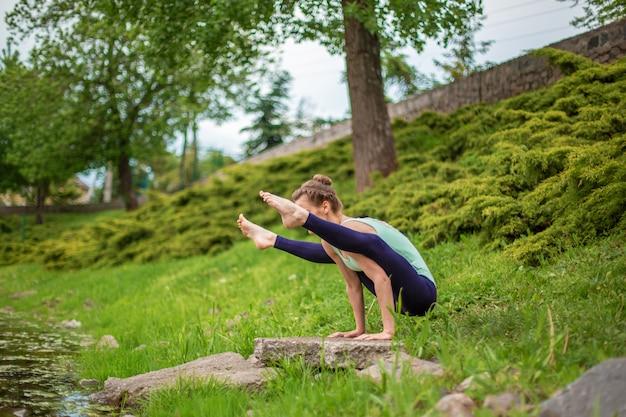Menina morena magro fazendo yoga no verão em um gramado verde à beira do lago