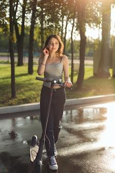 Menina morena, montando uma scooter elétrica ecofriendly em um parque em tempo ensolarado nas calçadas e ouve música