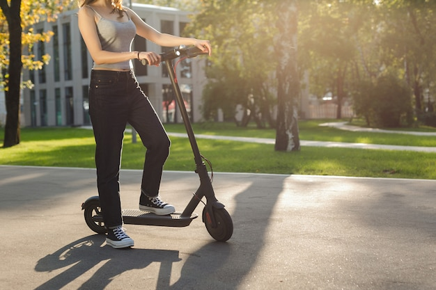 Menina morena, montando uma scooter elétrica ecofriendly em um parque em tempo ensolarado nas calçadas