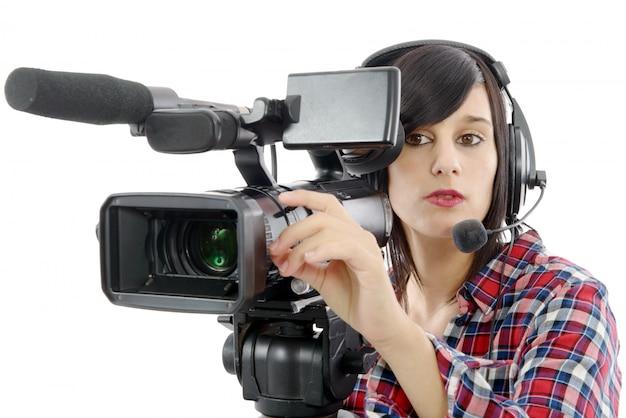 Menina morena muito jovem com uma câmera de vídeo profissional, em branco
