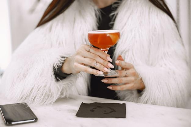 Menina morena. mulher com um casaco de pele branco. coquetel vermelho