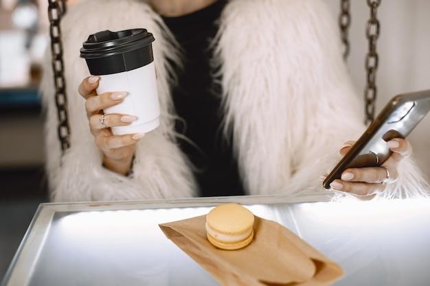 Menina morena. mulher com um casaco de pele branco. senhora com telefone e café.