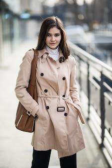Menina morena na rua em casaco de café e bolsa de couro marrom