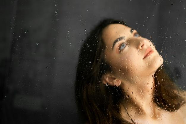Menina morena no chuveiro. gotas de água na tela do chuveiro. retrato
