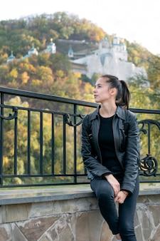Menina morena no parque, mosteiro em segundo plano. jovem e bela mulher descansando ao ar livre.