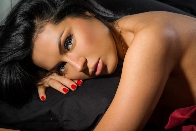 Menina morena nua posando na cama.