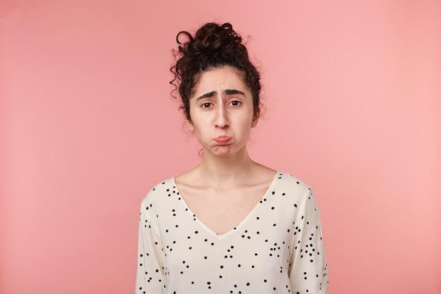 Menina morena ofendida triste chateada, faz beicinho com as bochechas é dominada por emoções negativas, de mau humor vestida de blusa com bolinhas, vai chorar, isolado no rosa