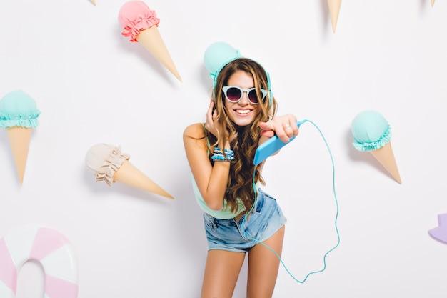 Menina morena otimista com pele bronzeada, usando acessórios da moda, olhando com um sorriso sincero. retrato de jovem rindo curtindo música na parede decorada com sorvete.