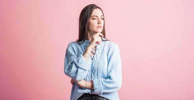 Menina morena pensativa em estúdio em fundo rosa