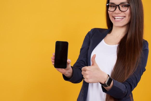 Menina morena posa com telefone, polegares para cima isolado