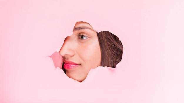 Menina morena posando através de um buraco de papel