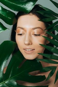 Menina morena posando com folhas exóticas