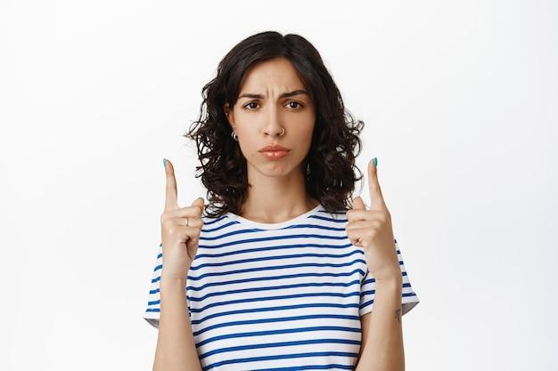 Menina morena preocupada franzindo a testa, apontando os dedos para cima e parecendo chateada, decepcionada com a má propaganda, expressa ciúme ou arrependimento, mostra algo injusto cruel no branco.