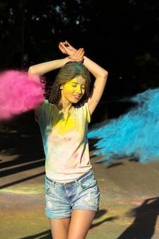 Menina morena satisfeita posando com pó de gulal explodindo no parque
