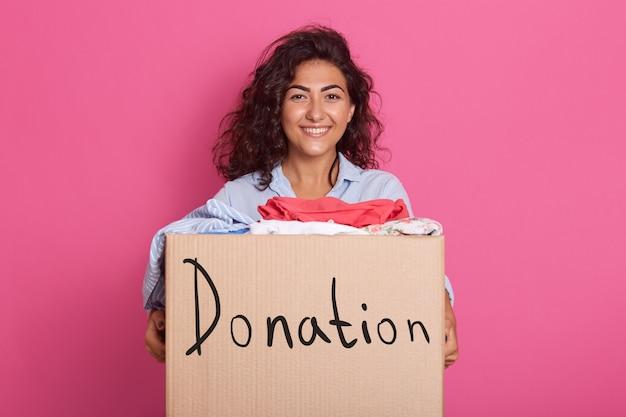 Menina morena segurando a caixa doadora cheia de roupas