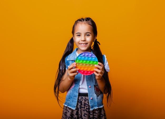 Menina morena segurando o brinquedo anti-stress pop em fundo amarelo com lugar para texto