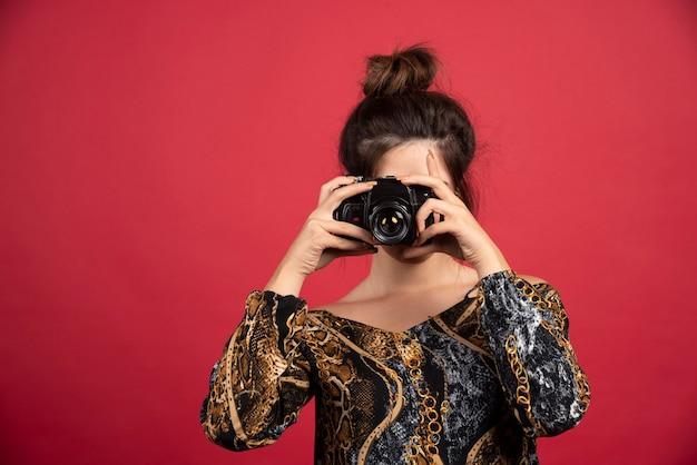 Menina morena segurando uma câmera dslr profissional e fazendo sessão de fotos.