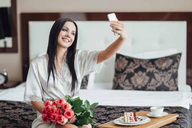 Menina morena senta na cama em seu quarto e faz um sephi em seu telefone branco, segura uma rosa encantadora no colo
