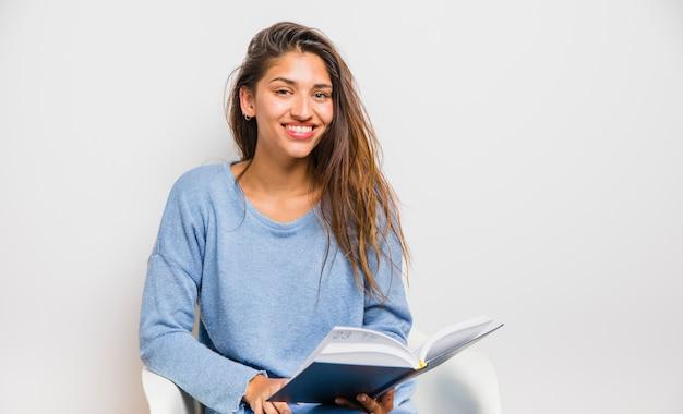 Menina morena sentada lendo um livro