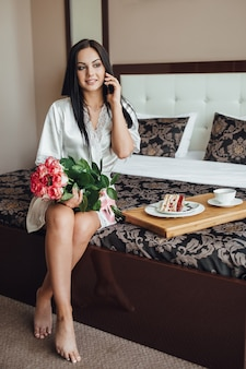 Menina morena sentada na cama do quarto dela, falando ao telefone e segurando um buquê de rosas nas mãos