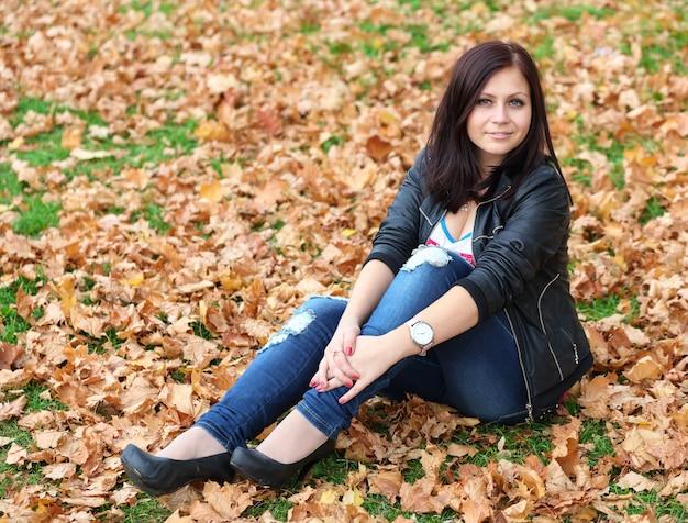 Menina morena sentada nas folhas de outono